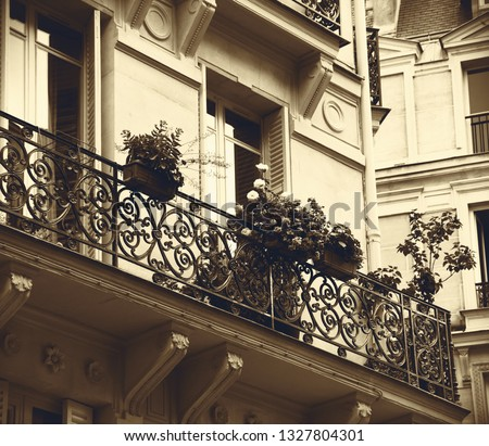 Balcony with forging railing decorated with roses and geranium flowers.Typical Parisian architecture. Building architecture detail. Sepia photo. Nostalgic Paris, old times concept.  #1327804301