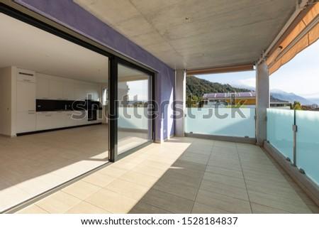 Balcony with travertine flooring, lilac facade. Sunny day. Nobody inside