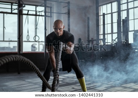 Bald athlete doing battle rope exercise at crossfit gym. Concentrated african man doing cross fit exercise while working out in gym. Focused man in sportswear training exercise.