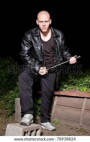 Bald athletic thug in black leather jacket and sport costume armed with police resin baton.Pumped gangster armed with stick.Big criminal guy on the backyard.Mafia member.Dangerous robber ready to rob.