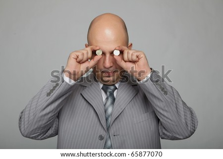 Bald businessman in a gray suit with a gray background with the coins on the eyes