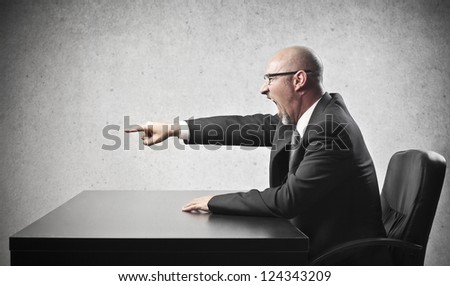 Bald businessman pointing his index finger at someone