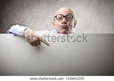 bald businessman shows with finger on blank billboard