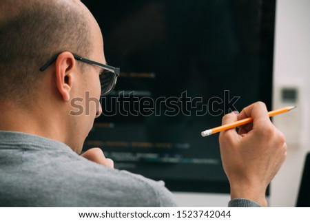 Bald caucasian programmer in glasses is sitting behind the desk, in front of black monitor, looking closely, analysing code lines, thinking through. Holding pencil in hand. Close up.