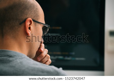 Bald caucasian programmer in glasses is sitting behind the desk, in front of black monitor, looking closely, analysing code lines, thinking through. He's very attentive and focused. Close up.