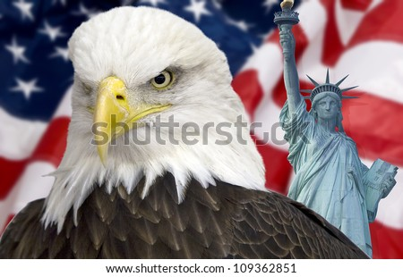 Bald eagle with statue of liberty and the american flag out of focus. - stock photo