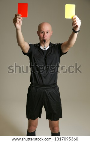 bald football referee on gray background. soccer referee raised both cards up. football referee in a black uniform holding a red and yellow card. the soccer referee shows two cards at once.