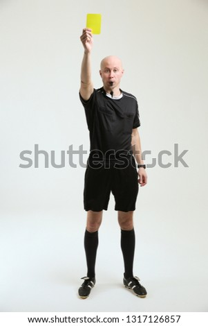 bald football referee on white background. soccer referee shows a yellow card and looks into the frame.  football referee in black uniform full-length on white background