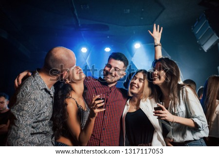 Bald guy kisses his wife. Beautiful youth have party together with alcohol in the nightclub.