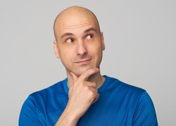 Bald guy wondering. Handsome man in blue shirt looking up and thinking. Isolated on gray background
