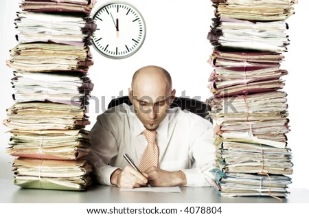 Bald headed businessman surrounded by stacks of files.  Concentrating on paperwork in front of him. Clock is visible in background.