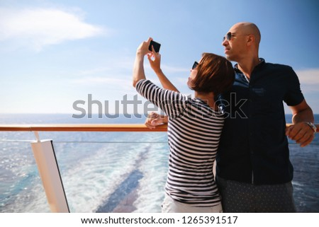 bald man and brunette woman traveling on cruise liner ship and taking pictures from smartphone on balcony