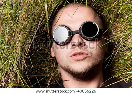 bald man in grass stare to all of you through round glasses, think about it