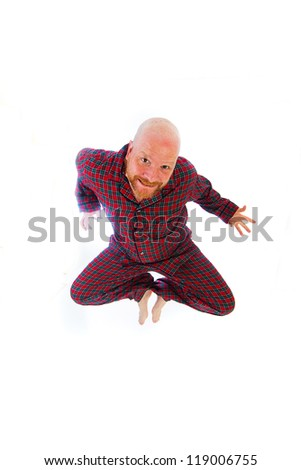 Bald man jumping in his flannel pajamas