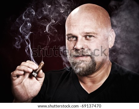 bald man with a beard smokes a cigar