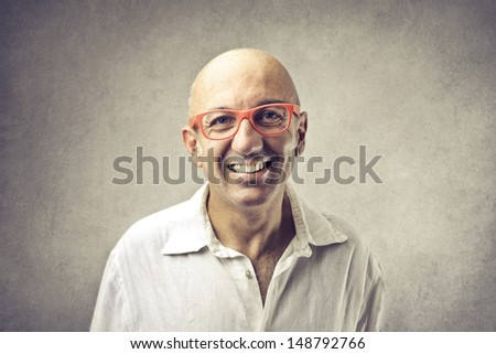 bald man with glasses smiling