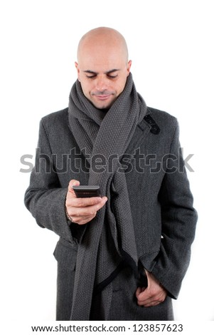 Bald man with tweed coat and scarf using his smart phone smiling. Isolated
