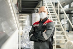 Bald mature worker of contemporary large polymer processing factory in workwear and protective mask crossing arms by chest in warehouse