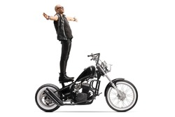 Bald punk daredevil standing on a chopper motorbike isolated on white background