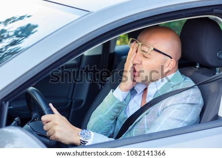 Bald stylish man in glasses rubbing face and looking embarrassed while sitting in car and driving on road having problems with traffic.