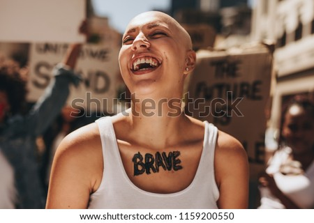 Bald woman laughing outdoors during a protest. Brave woman with group of protesters in background.