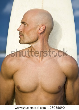 Bald young man holding a surfboard