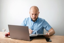 Bald young man with beard reading encyclopedia book and working online on his laptop at the wooden table in home office, white wall as background. Business, freelance or study concept.