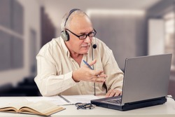 Balding old man in headset explains emotionally sitting in front of the laptop computer.  Retired man works as freelancer in internet from home office. Horizontal indoors mid shot on blurry background