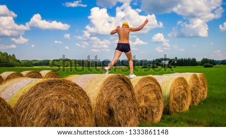 Bales of hay in Agricultural fields. Guy jumps from bale to bale #1333861148