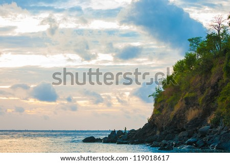 Bali cliffs with silhouetted fisherman looking out to sea