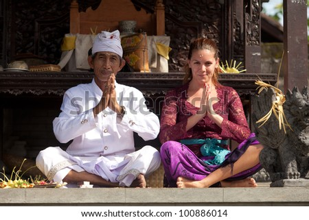 BALI - FEBRUARY 1. Priest praying with worshipper in temple for Galungan ceremony on February 1, 2012 in Bali, Indonesia. Galungan's a Balinese holiday occuring every 210 days lasting 10 days.
