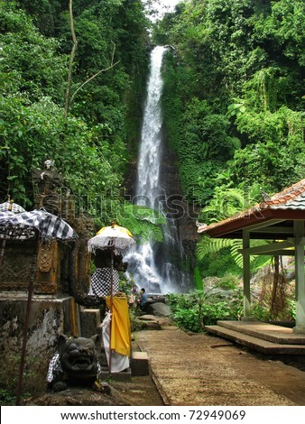 Bali: impressive Gitgit waterfalls, surrounded by beautiful wild nature and a lovely temple. Near Lovina, north Bali (Indonesia)