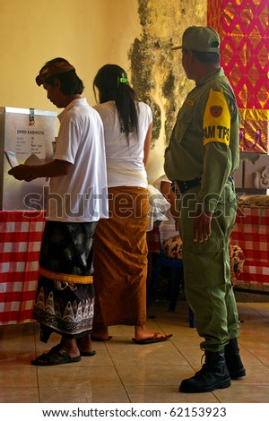 BALI, INDONESIA - APRIL 9: Security guard overlooking voting in a polling station on April 9, 2009 in Denpasar, Baliin only the second direct election since the fall of the Suharto dictatorship in 1998.