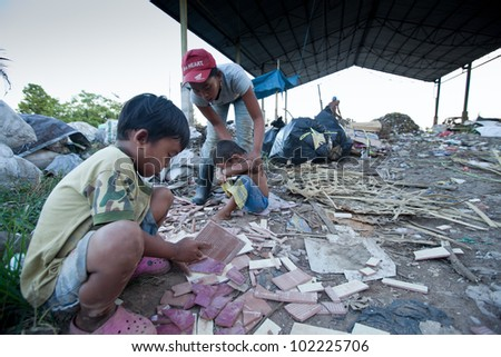 BALI, INDONESIA - APRIL 11: Unidentified children and his parents working in a scavenging at the dump on April 11, 2012 on Bali. Bali daily produced 10,000 cubic meters of waste.