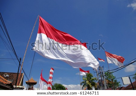 BALI, INDONESIA - AUGUST 17: Indonesian flags raise across Indonesia for independence day on August 17, 2010, Denpasar, Bali. This national holiday is one of the biggest events of the year.