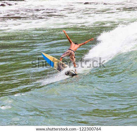 BALI, INDONESIA - JANUARY 13: Unidentified young surfer on the board on January 13, 2012. Dreamland beach, Bali, Indonesia. The Dreamland is one of the most popular surfing areas of Bali. - stock photo