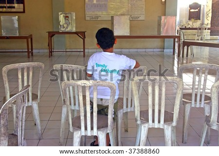 BALI, INDONESIA - JULY 8, 2009: A boy sitting in front of polling boxes at a polling station, in Indonesia's Presidential election. Tuban, Bali, Indonesia. July 8, 2009.