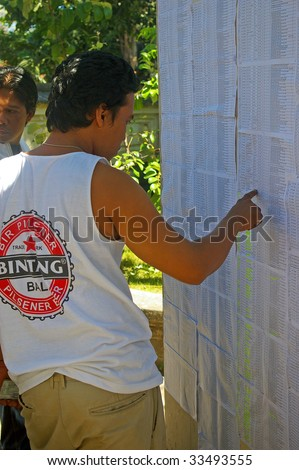 BALI, INDONESIA - JULY 8, 2009: A young man searching for his name on a registration list, on the day of the Presidential election. Tuban Bali, Indonesia. July 8, 2009.