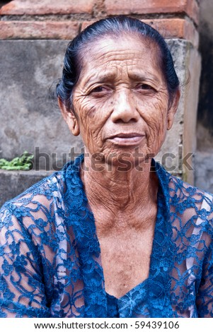 BALI, INDONESIA - JULY 14: BALINESE CREMATION CEREMONY: an old woman wears her elegant dress sits on the street waiting for the ceremony to begin on July 14, 2010 in Bali.