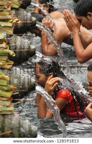 BALI, INDONESIA - JULY 15: Balinese Hindu families come to the sacred springs of Tirta Empul in Bali, Indonesia to pray and cleanse their soul on July 15, 2012.