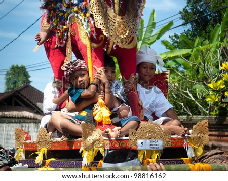 BALI, INDONESIA, JULY 14: unidentified Balinese children participate at the parade during the cremation ceremony in Penestanan, Bali on July 14th 2010.