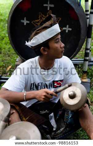 BALI, INDONESIA-JULY 14: unidentified Balinese musician plays a traditional musical instrument  during the cremation ceremony in Penestanan, Bali on July 14, 2010.