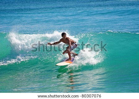 BALI, INDONESIA - JULY 27: Unidentified young man surfing the waves on Dreamland beach on July 27, 2010 in Bali, Indonesia. The Dreamland is one of the most popular surfing areas of Bali.