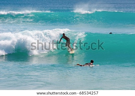BALI, INDONESIA - JULY 27: Unidentified young man surfs the waves on July 27, 2010. Dreamland beach, Bali, Indonesia. The Dreamland is one of the most popular surfing areas of Bali.