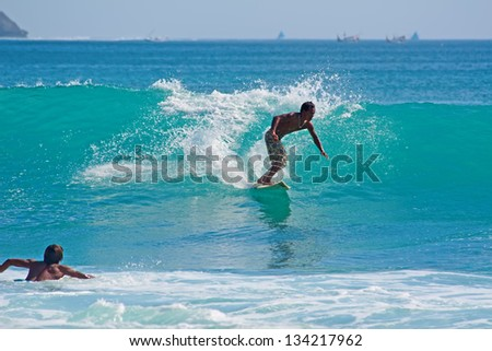 BALI, INDONESIA - JULY 27: Unidentified young men surfing the waves on July 27, 2010. Dreamland beach, Bali, Indonesia. The Dreamland is one of the most popular surfing areas of Bali.