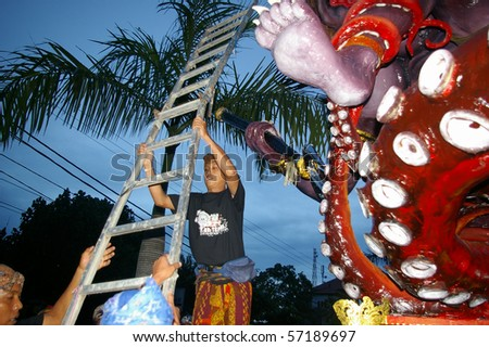 BALI, INDONESIA - MARCH 7: About to climb a giant statue at the Hindu festival of Pengrupukan in Nusa Dua, 2008. The annual festival is to roust out devils which have gone into hiding on the island.