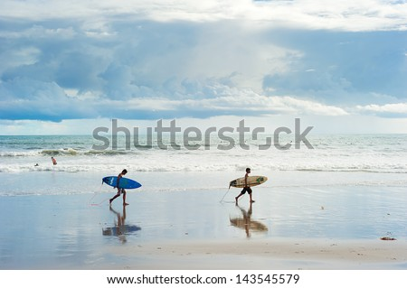 BALI, INDONESIA - MARCH 16: Local boys walking with a surfboards on the beach on March 16, 2013 in Bali island; Indonesia. Bali is one of the top of world surfing destinations.