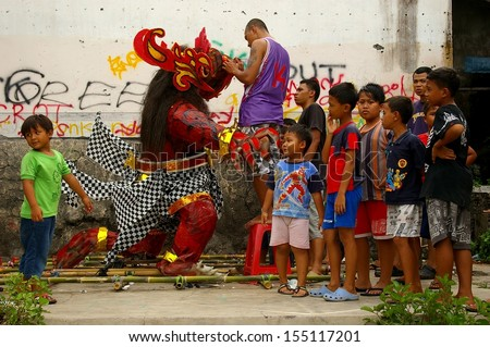 BALI, INDONESIA - MARCH 7: Unidentified boys with a monster statue for the Hindu festival Pengrupukan March 7, 2008 in Nusa Dua, Bali. This Celebrates the Balinese New Year and the arrival of spring.