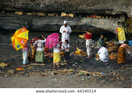 BALI, INDONESIA - NOVEMBER 17: Balinese pilgrims at Tanah Lot temple on November 17, 2009, Tanah Lot, Bali. The temple has been part of Balinese mythology for centuries.