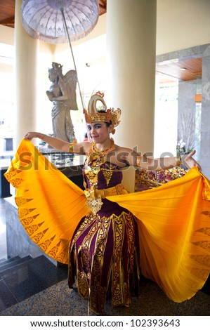 BALI, INDONESIA - NOVEMBER 15: young balinese female dancer in traditional dress  welcomes arriving tourists on November 15,2011 on Bali,Indonesia. At 2010, Bali received 2.57 million foreign tourists